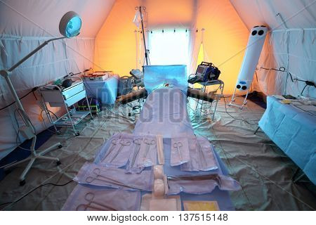 Inside the operating room with a waxwork on the operating table and tools in a field hospital