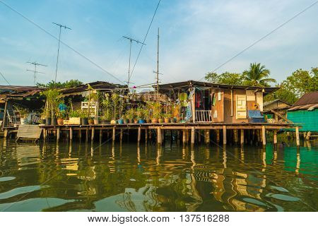 Stilt houses built above river Mae Klong in Amphawa, rural Thailand. Beautiful countryside landscape at sunset.