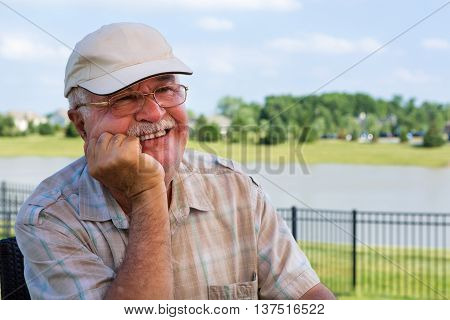 Happy elderly man wearing glasses and a peaked cap sitting on an outdoor patio overlooking a pond giving the camera a beaming smile