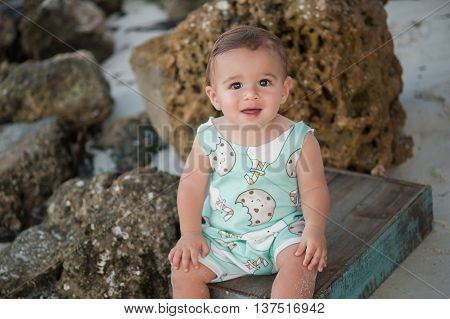 A one year old baby boy sitting on a blue wooden crate. Shot outdoors on a beach with rocks in the background.