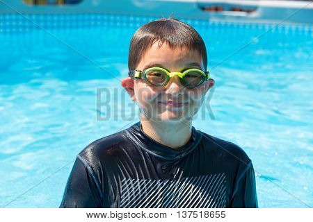 Soaked single grinning boy in swim shirt and goggles at outdoor swimming pool during summer season