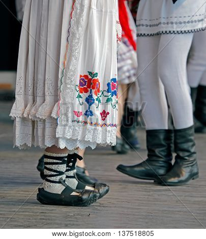 Feet of dancers and clothes in traditional Romania folk dances.