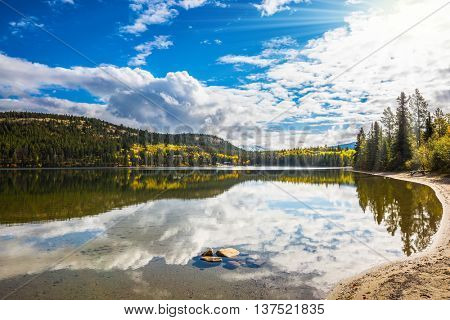 Pyramid Mountain and cumulus clouds is reflected in Pyramid Lake. Cold autumn morning in the Rocky Mountains, Canada