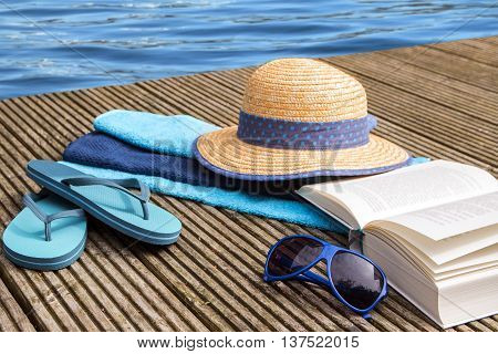 summer vacation blue water and accessories for beach holidays as straw hat, flip flops, turquoise towels and a book on a wooden bathing pier at the pool selected focus and narrow depth of field