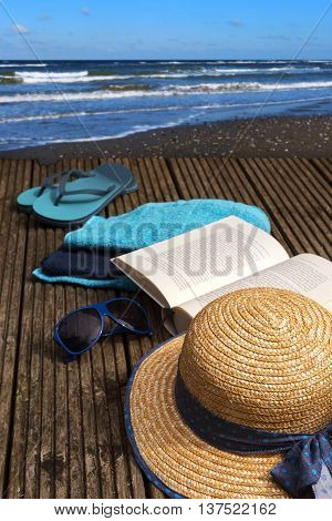 summer vacations at the seaside shore accessories for beach holidays on a wooden bathing platform directly at the sea selected focus and narrow depth of field