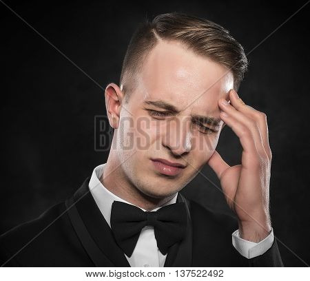 Young man holding his head feeling a headache or intensely thinking.