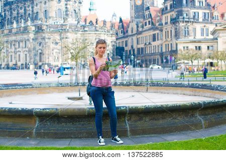 Young woman read travel guid in Dresden. Germany
