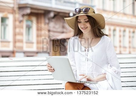 Happy young woman working with a laptop sitting on a bench. She smiles. Student is white with brown hair. The woman dressed in brown jeans, a white tunic. On her head is  hat and sunglasses. Summer.