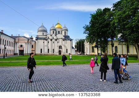 VELIKY NOVGOROD RUSSIA - JUNE 11 2016. Unidentified tourists walking and taking the shots near St Sophia cathedral in Veliky Novgorod Russia