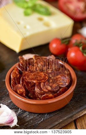 closeup of an earthenware bowl with some slices of Spanish chorizo, a pork sausage typical of Spain, on a rustic wooden table with a piece of cheese, some tomatoes and garlic cloves in the background