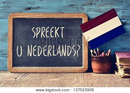 a chalkboard with the question Spreekt u Nederlands?, do you speak Dutch? written in Dutch, a pot with pencils, some books and the flag of the Netherlands on a wooden desk