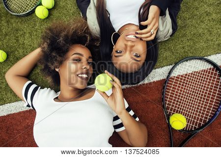 young pretty girlfriends hanging on tennis court, fashion stylish dressed swag, best friends happy smiling together. lifestyle people concept