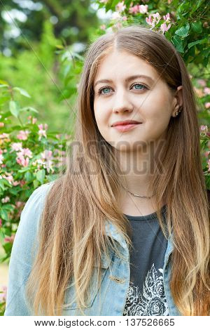 Portrait of a young beautiful girl of Caucasian appearance with very beautiful eyes. Amazing eye color. Girl on a background of a blossoming tree outdoors in the summer