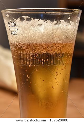 A close up shot of a clod glass of beer.