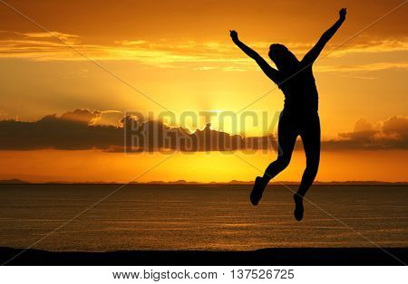 Young woman who is jumping at the beach