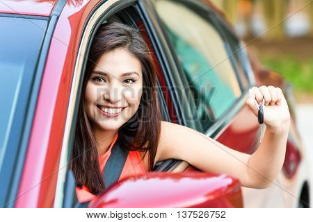 Woman holding up keys to her new car