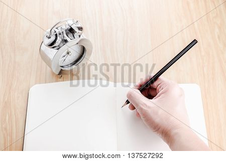 Hand Holding Black Pencil And Writing On Blank Open Notebook With Alarm Clock Beside It On Wooden Ta