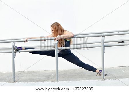 Portrait of a young woman stretching Fit legs and eyes closed, enjoying the sun, doing exercises against a wall background with copy space for your text or message content