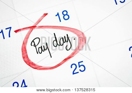 Pay day written with red mark on a calendar page.