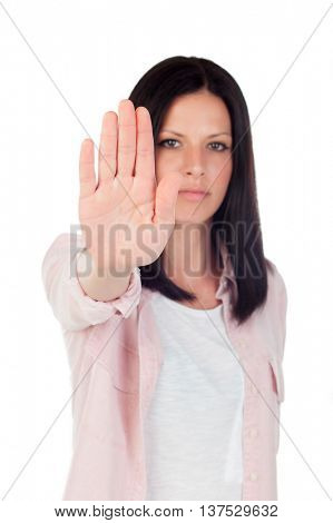 Young brunette girl making stop sign on a white background. Focus on hand