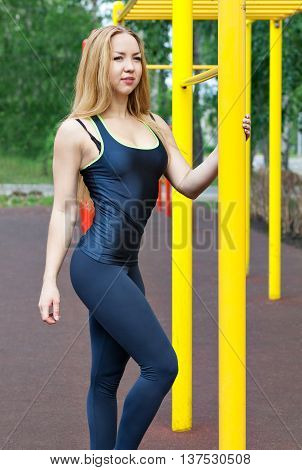 Blond fitness woman in sportswear with a perfect body fitness workout on the street to do the exercises on the horizontal bar. sexy young fitness girl on the street gym.