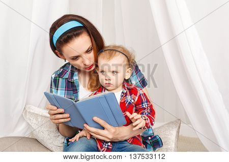 Mother and daughter read the e-book. Fairy tales. Young mother and baby daughter hugging. Girls dressed in plaid shirt. Family education