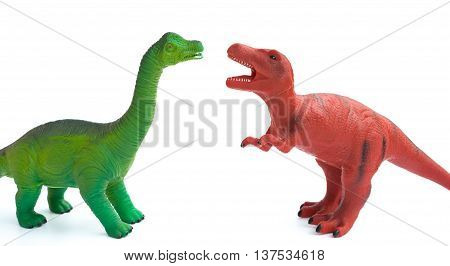 green brachiosaurus and red tyrannosaurus toys on a white background