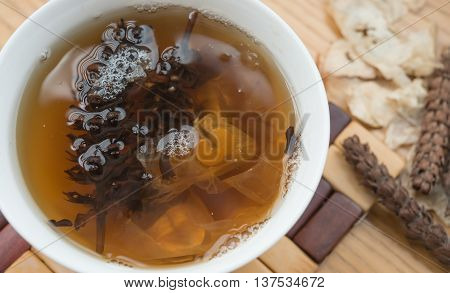 bowl of Chinese herbal tea with raw herbal nearby