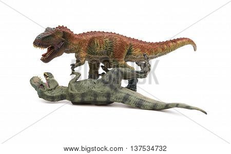 two tyrannosaurus toys on a white background one stands and the other lays down