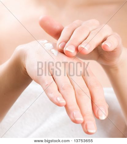 Female applying moisturizer to her Hands after bath.Skincare concept