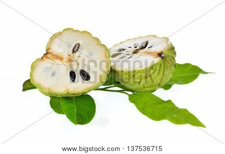 half cut custard apple with leaves on white background