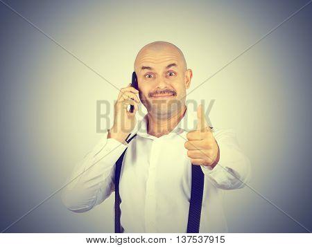 Bald Mustachioed Man Talking On The Phone.