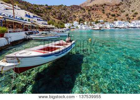 LOUTRO, CRETE, GREECE - JULY 2, 2016: Small motorboat at clear water bay of Loutro town on Crete island, Greece