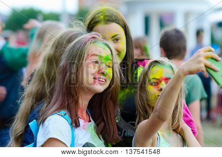 GOMEL BELARUS - JULY 6 2016: Group of teenage girls takes selfie during festival of colors (Holi Festival or ColorFest) in Gomel Belarus