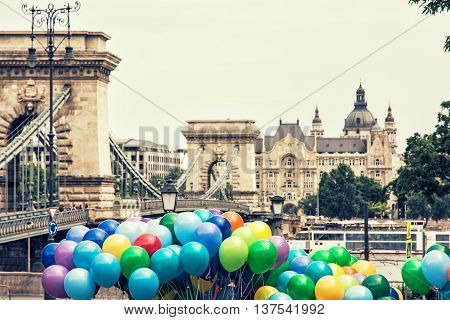 Famous Chain bridge Saint Stephen's basilica and colorful balloons in Budapest Hungary. Cultural heritage. Entertainment event. Travel destination. Retro photo filter. Tourism theme. Architectural theme.