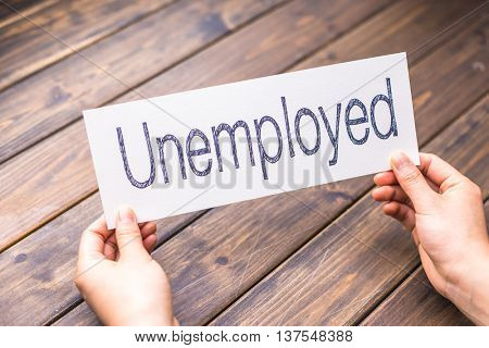hands hold white paper with word unemployed
