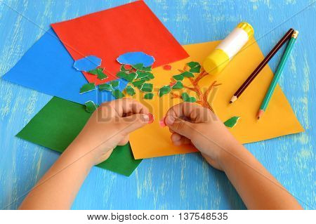 Child tears a red paper into small pieces. Child holds colored paper in his hands. Pencils, glue stick on wooden background. Fun crafts for kids. Idea to develop fine motor skills for babies
