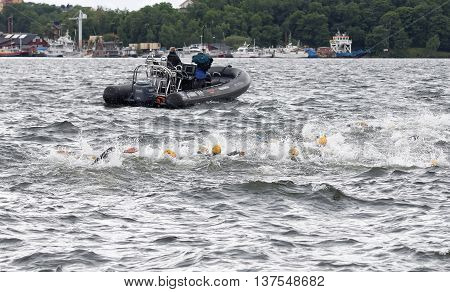 STOCKHOLM - JUL 02 2016: Chaos of swimming arms in the water and rescue boat in the Women's ITU World Triathlon series event July 02 2016 in Stockholm Sweden