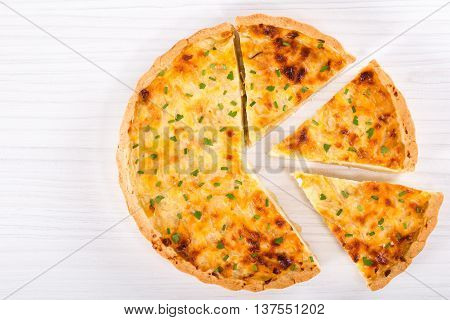 onion cheese quiche or pie sprinkled with parsley and spring onion cut into portion on white table top view blank space left
