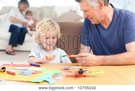 Little boy drawing with his grand father at home