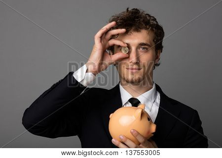 Elegant Man With Piggybank On Gray Background