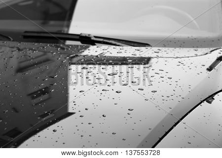 Reflection of house and raindrops on the hood of the car in the parking lot.