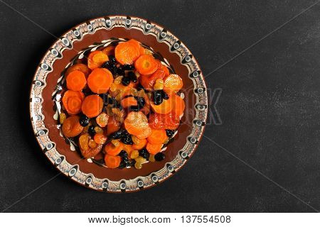 Traditional Jewish Tzimmes dish prepared with carrot and dried fruits on the black background
