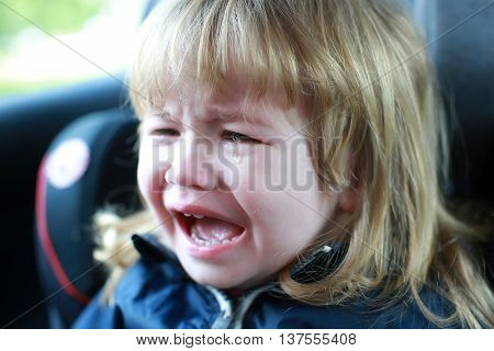 small boy child with facial emotions on unhappy crying face and long blonde hair sitting in car with tear on cheek closeup