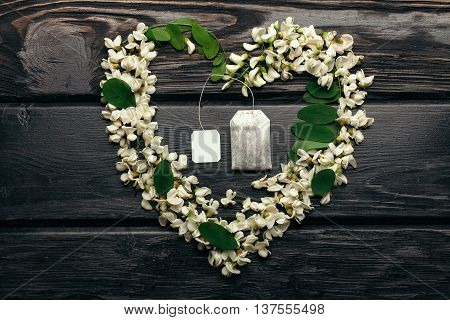 Teabag with tag in heart wreath of white acacia blossoming flower petals and green leaves on dark timber background