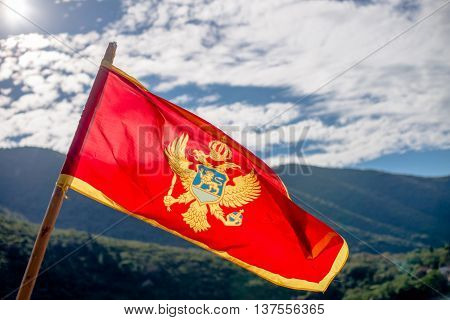 Montenegro flag flying in the background of the mountains