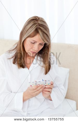 Sick woman taking her pills at home