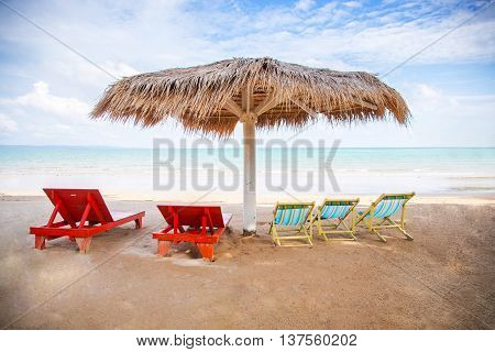 beach with thatched umbrellas on the shore of the Koh mak island in Thailand
