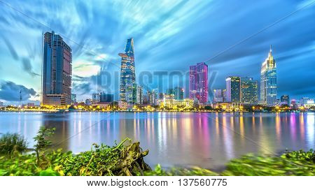 Ho Chi Minh City, Vietnam - July 7th, 2016: Beauty skyscrapers light illuminates smooth along river, sky clouds glide through, hyacinth drifting foreground patches adorn urban development country