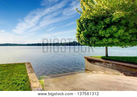 Beautiful Landscape With Water View And Concrete Way To The Water For Boat Launching.